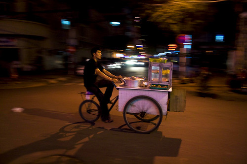 hawker paddling on the streets of ho chi minh city, vietnam
