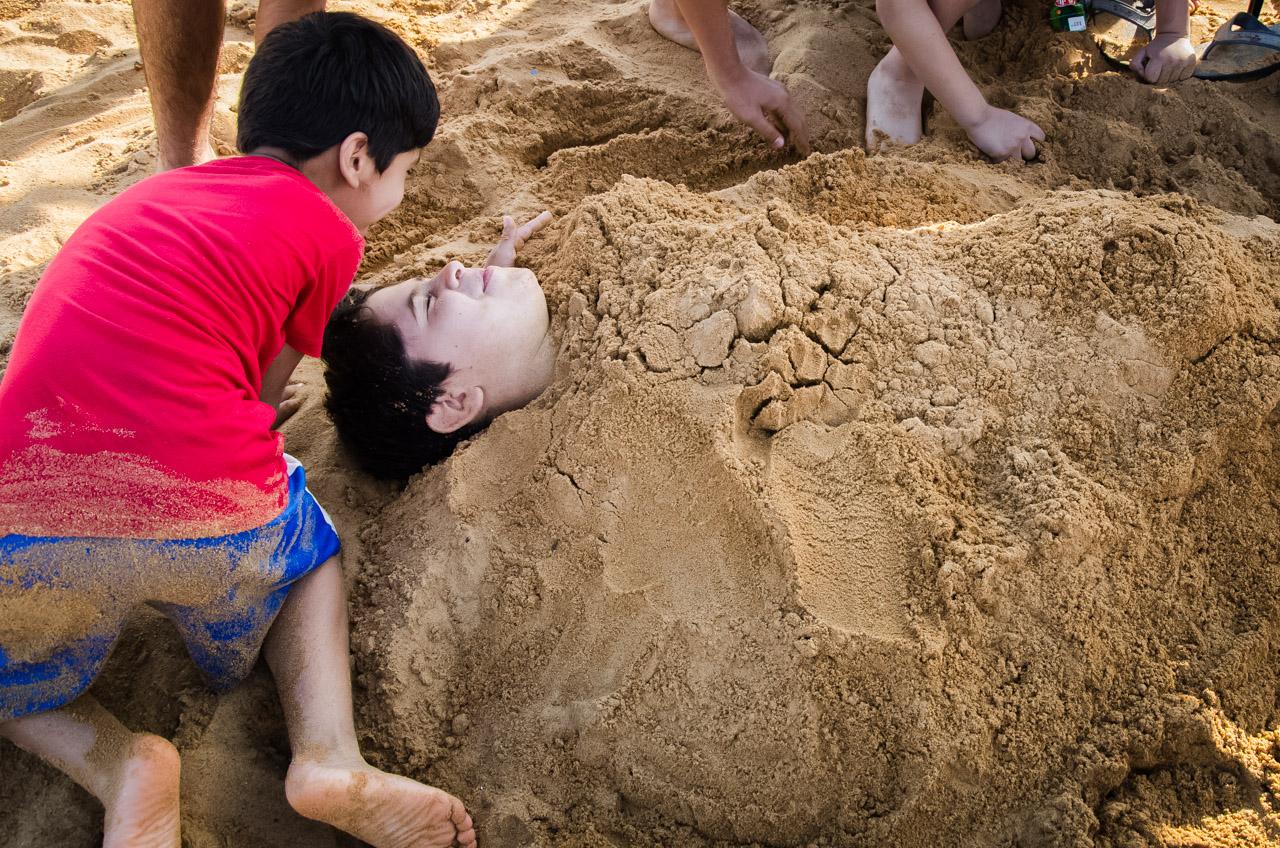 Los niños se divierten en la arena enterrando a uno de sus amigos, en la plata San José de Encarnación. (Elton Núñez)
