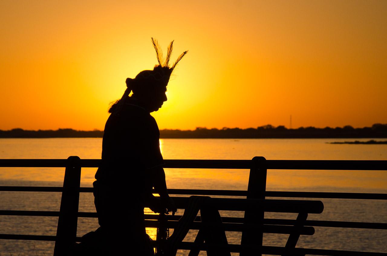 Un indígena Maká recorre la costanera de Asunción vendiendo artesanías de su pueblo mientras transcurre el atardecer. (Elton Núñez)