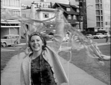 "Still frame from CBC Vancouver's ""The Be-In"" (1967), woman with streamers entering Stanley Park."