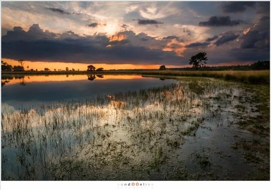 De zon achter een donkere wolkenpartij, mooie kleuren en reflecties in een traditionele compositie