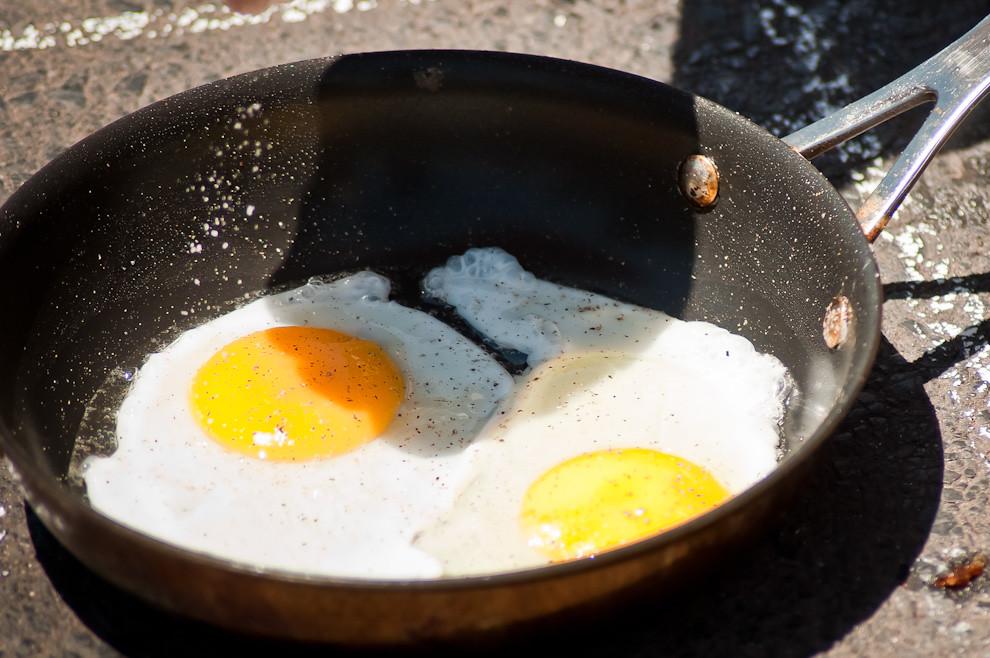 Una toma cercana de los huevos cocinados con el calor del asfalto y el sol, con sal y un poco de pimienta se servía con panceta y polenta grillada. Todos estos elementos cocinados con el calor del sol. (Elton Núñez)