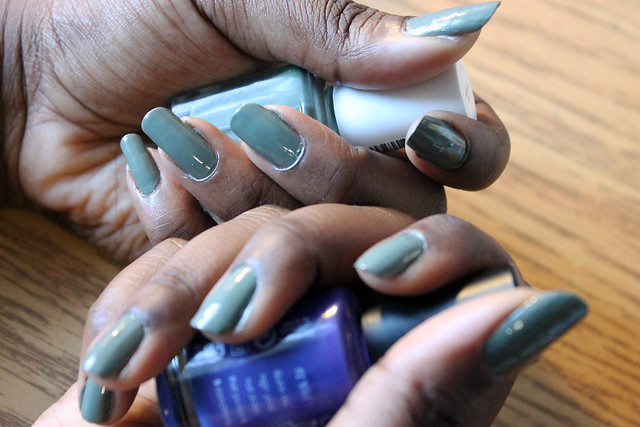 hands with green nails holding two bottles of nail polish, one green and one purple