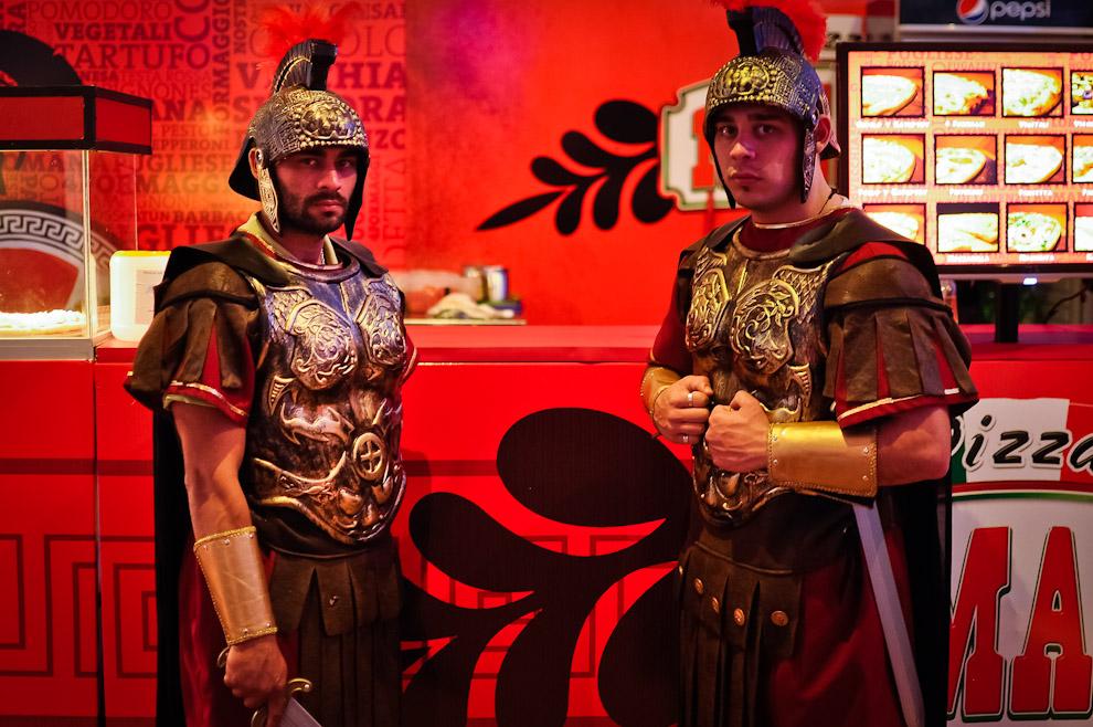 """Dos hombres disfrazados como soldados romanos posan frente al stand de la famosa pizería """"Romana"""" en el show room del Paraguay Alta Moda en su edición Primavera-Verano 2013/2014. (Elton Núñez)"""