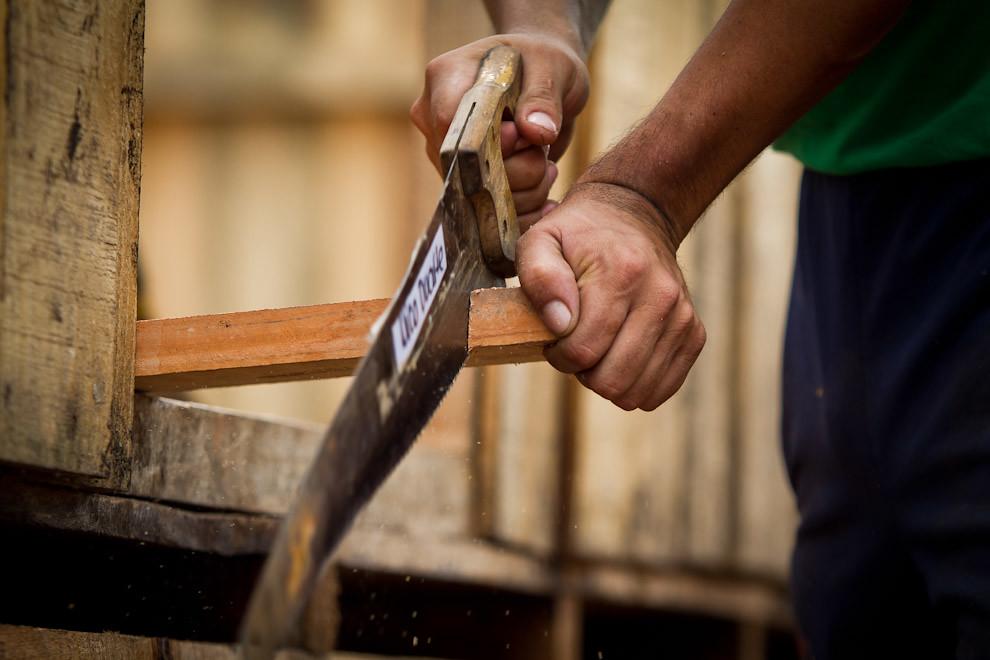 Serruchando un listón de madera para una de las vigas del techo. (Tetsu Espósito - Lambaré, Paraguay)