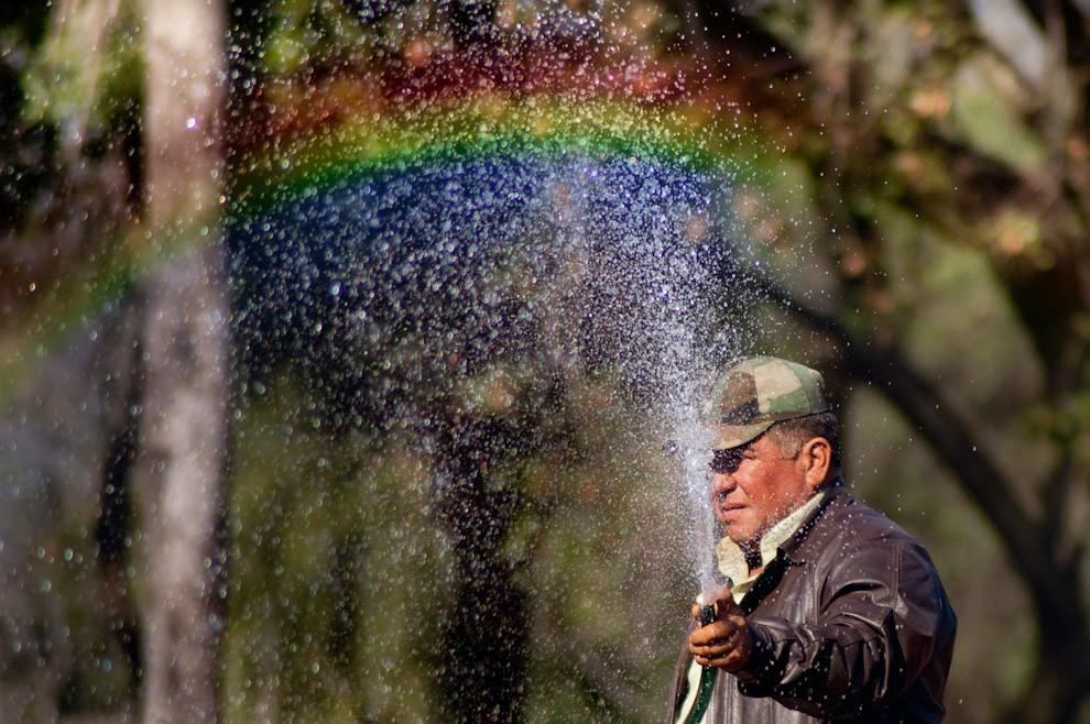 En una radiante mañana del domingo 5 de Setiembre un señor riega su patio con agua corriente dejando ver un arcoiris en el reflejo del agua con el sol. (Elton Núñez - Luque, Paraguay)