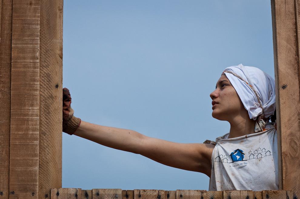 Una voluntaria ayuda a su compañero durante la instalación de los paneles de la casa que serían las paredes una vez armados. (Elton Núñez - Asunción, Paraguay)