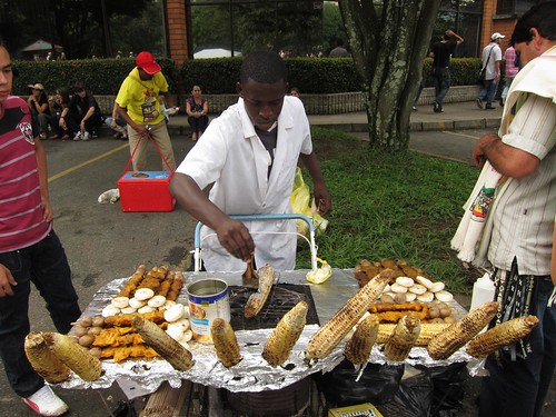 A street vendor cooks up corn on the cob, a popular snack food.