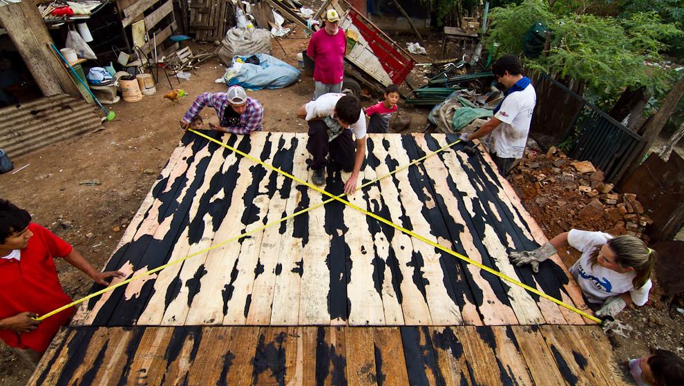 Realizando medidas finales sobre el piso de la vivienda antes de iniciar la colocación de las paredes. (Tetsu Espósito - Lambaré, Paraguay)