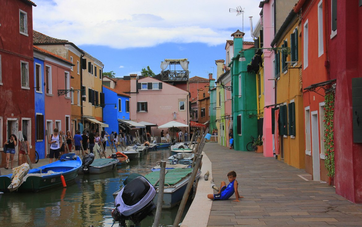 A local boy sits outside his house in Burano Italy