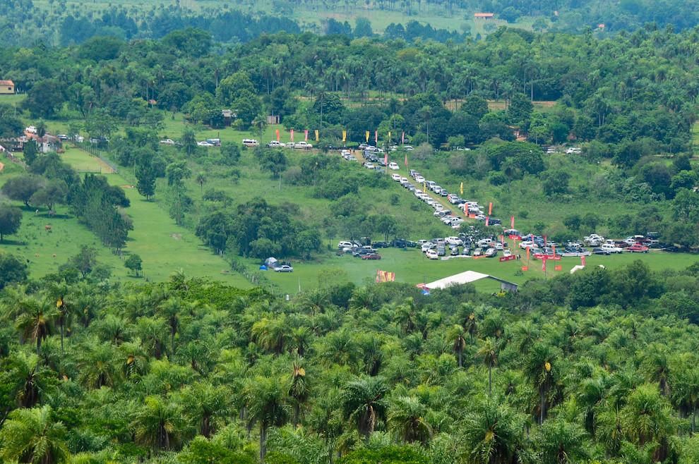 Vista de la Quinta Mandu'arã desde uno de los picos del Cerro Naranjo, donde se puede ver la cantidad de vehículos estacionados en la entrada, los estandartes de publicidad de los auspiciantes a lo largo del predio. (Elton Núñez - Piribebuy, Paraguay)