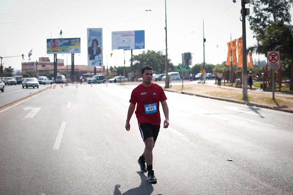 Un joven toma un descanso mientras continúa su carrera en la categoría 48 kilómetros del Maratón del Bicentenario. (Elton Núñez - Asunción, Paraguay)