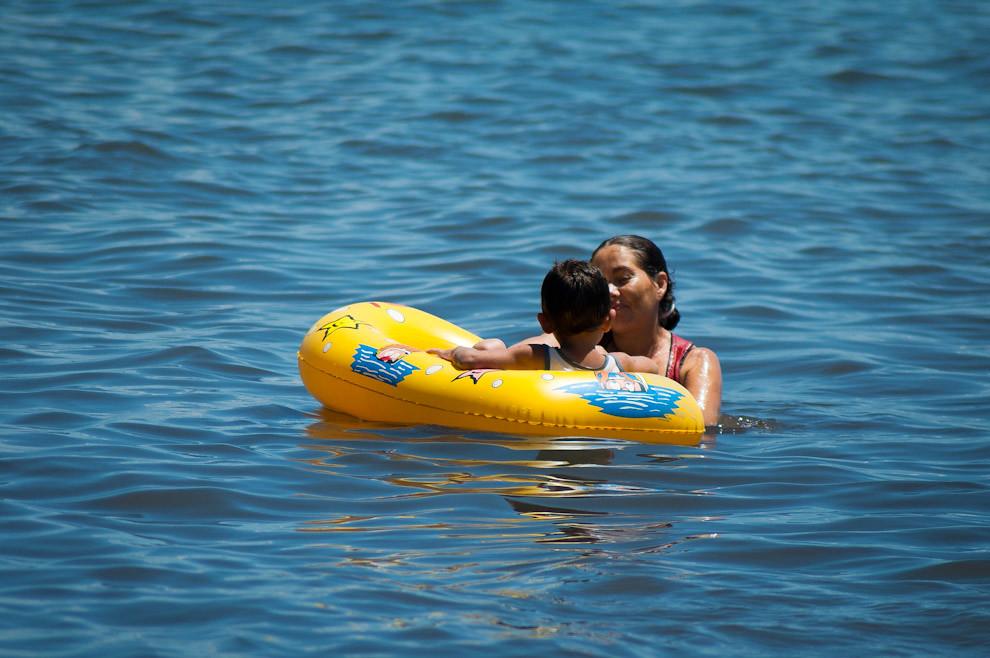 Una madre se divierte con su hijo en las aguas del Lago Ypacaraí en el domingo 23 de Enero al mediodía. A pesar de las declaraciones de la prensa y de los representantes de la Secretaria del Ambiente de que las aguas del Lago siguen contaminadas, eso no detiene a los veraneantes. (Elton Núñez - Ypacaraí, Paraguay)