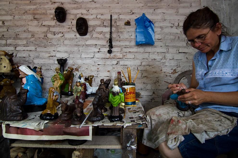 Una artesana da los  ultimos toques de pintura a uno de los personajes del pesebre que pondrá a la venta en su local de Areguá, una ciudad famosa y reconocida por su artesanía en la cerámica. (Tetsu Espósito - Areguá, Paraguay)