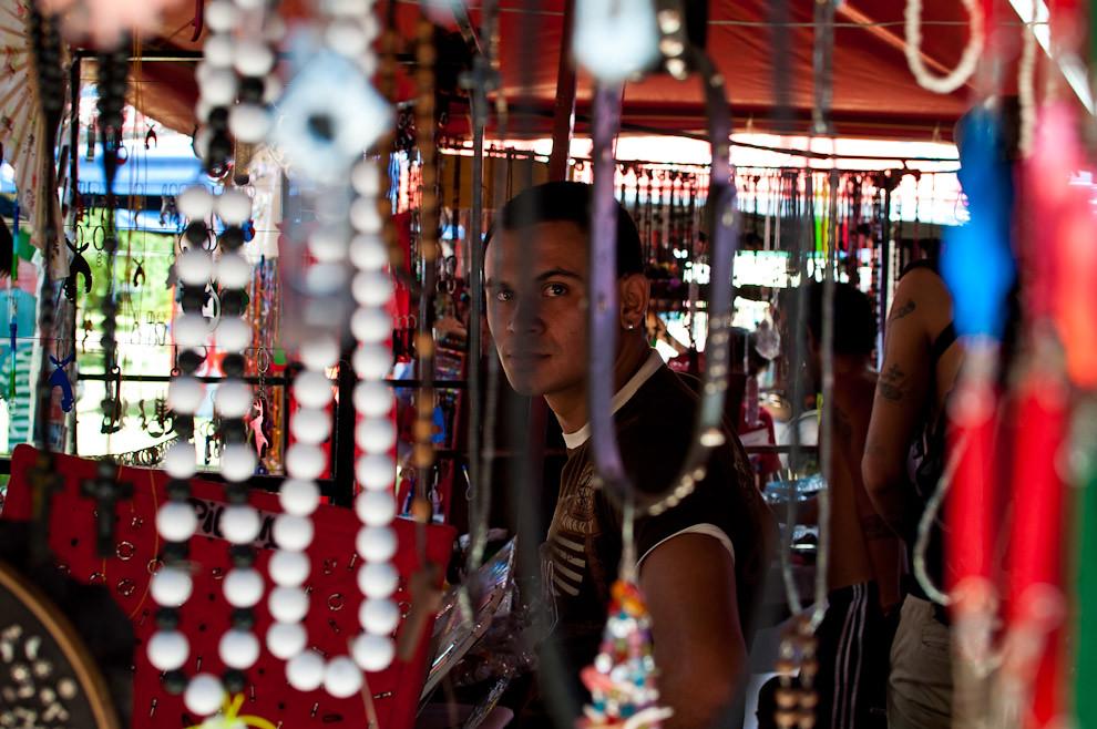 Un vendedor de joyas, adornos y souvenirs atiende su negocio bajo el calor abrazante del domingo 23 de Enero pasado, corresponde a uno de los negocios de artesanías que se instalaron en la plaza al lado de la Iglesia de San Bernardino. (Elton Núñez - Ypacaraí, Paraguay)