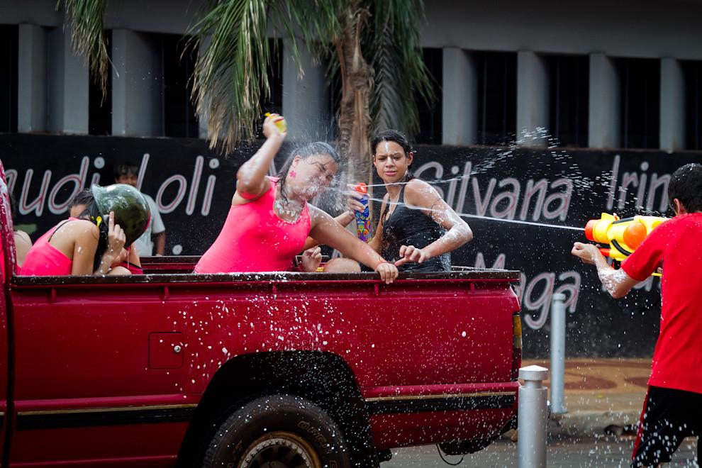 Tiro al blanco: un joven apunta y dispara contra una señorita a bordo de una camioneta, quien se defiende del ataque lanzando un globito de agua. (Tetsu Espósito - Encarnación, Paraguay)