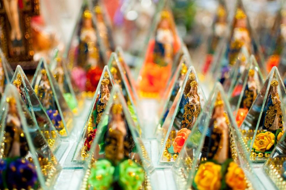 Imagenes de la Virgen de Caacupé en minaturas son vendidas en las aceras de la Ciudad, en las calles rumbo al Ycuá. Estas imagenes guardadas en triángulos de cristales son vendidas a un costo aproximado de 10.000 gs cada uno, la gente los lleva y los hace bendecir por un sacerdote de la Basílica. (Elton Núñez - Caacupé, Paraguay)