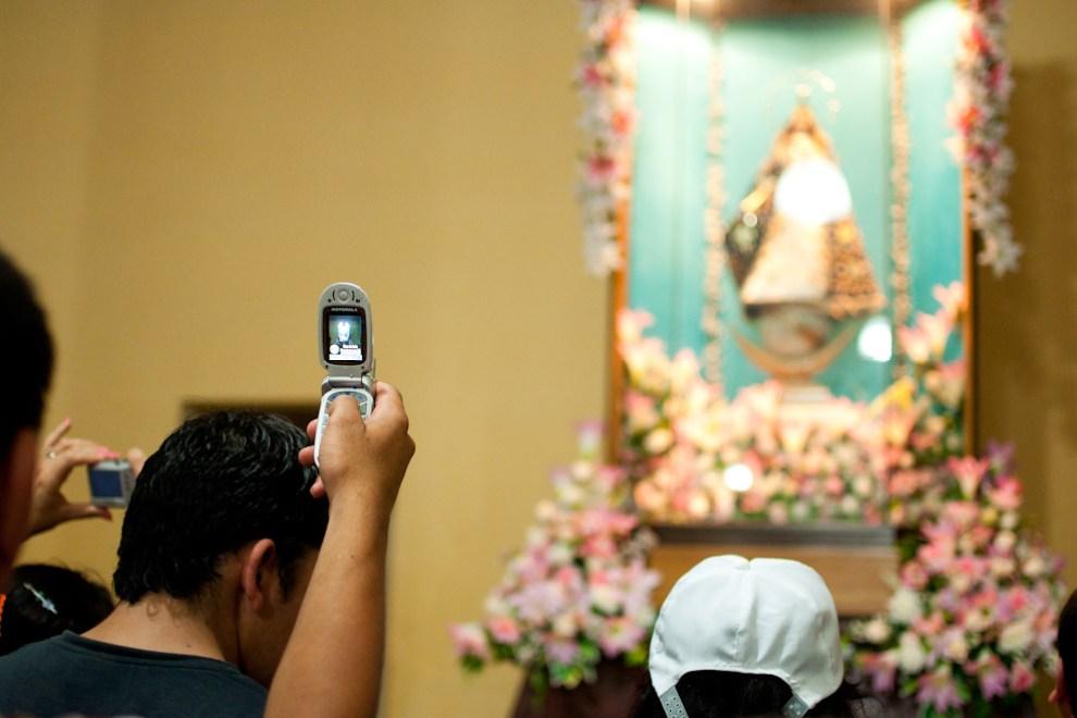 Un Visitante de la Virgen lleva un recuerdo en su celular en la noche del 7 de Diciembre durante la Vigilia de Oración esperando las 00:00 hs, mucha gente se congrega en la capilla bajo la Basílica para acercar sus oraciones y saldar sus promesas, entre ellos muchos sacan sus cámaras digitales o sus celulares y obtiene una imagen de recuerdo. (Elton Núñez - Caacupé, Paraguay)