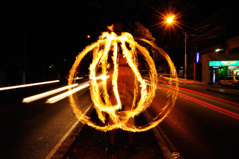 Un malabarista conocido como Pipi entretiene al público con sus habilidades con 3 antorchas encendidas, sobre el paseo central de la Avenida Sacramento. (Elton Núñez - Asunción, Paraguay)