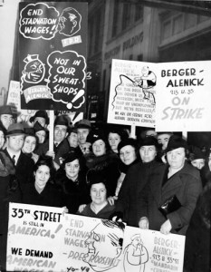 "Workers on W. 35th St. between 7th and 8th Ave., the area known as China Town, strike for improved conditions, 1940.  One sign suggests Franklin D. Roosevelt would say ""End Starvation Wages"" and Berger - Alenick would reply ""Not in Our Sweat Shops"""