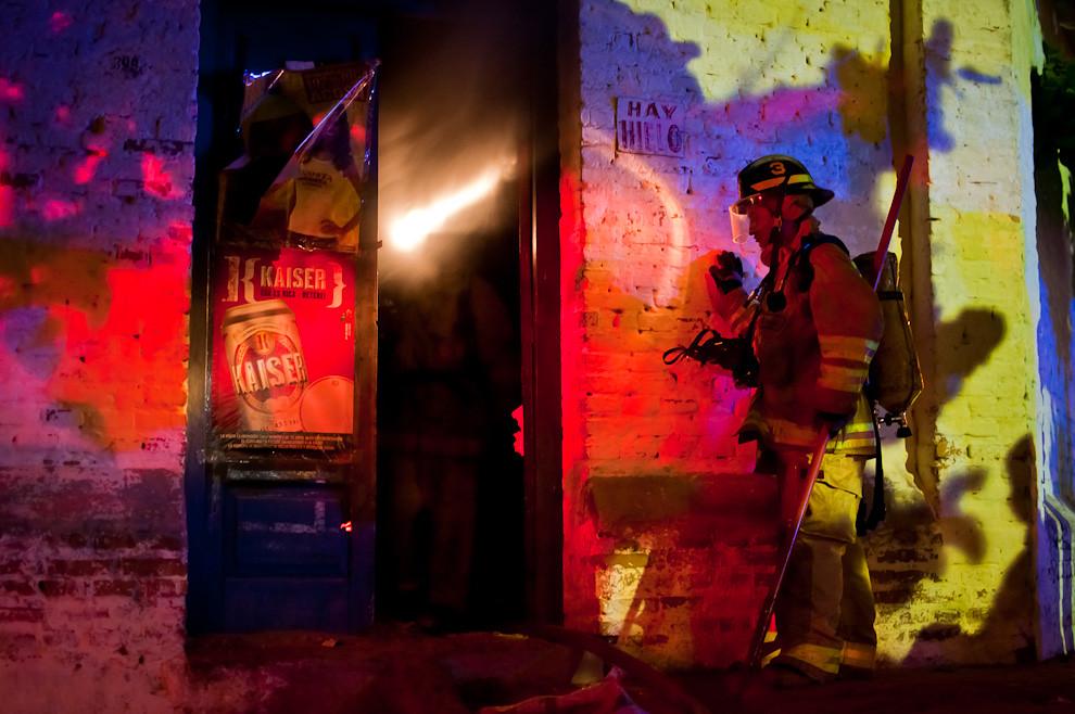 """Los bomberos voluntarios de la 3ra. Compañía """"Sajonia"""", trabajan en la extinción del incendio producido en el interior de una humilde despensa, en un domicilio de Sajonia el pasado 31 de marzo en horas de la madrugada. La casa afectada quedaba muy cerca del cuartel de bomberos por lo que el auxilio no tardó en llegar. Una situación notable es que las comunidades más cercanas al cuartel de bomberos son las más colaboradoras, ellos tienen muy en cuenta el cuidado mútuo que debe haber entre los bomberos y la gente, es por eso que de vez en cuando aportan a la compañía importantes suministros. (Elton Núñez)."""