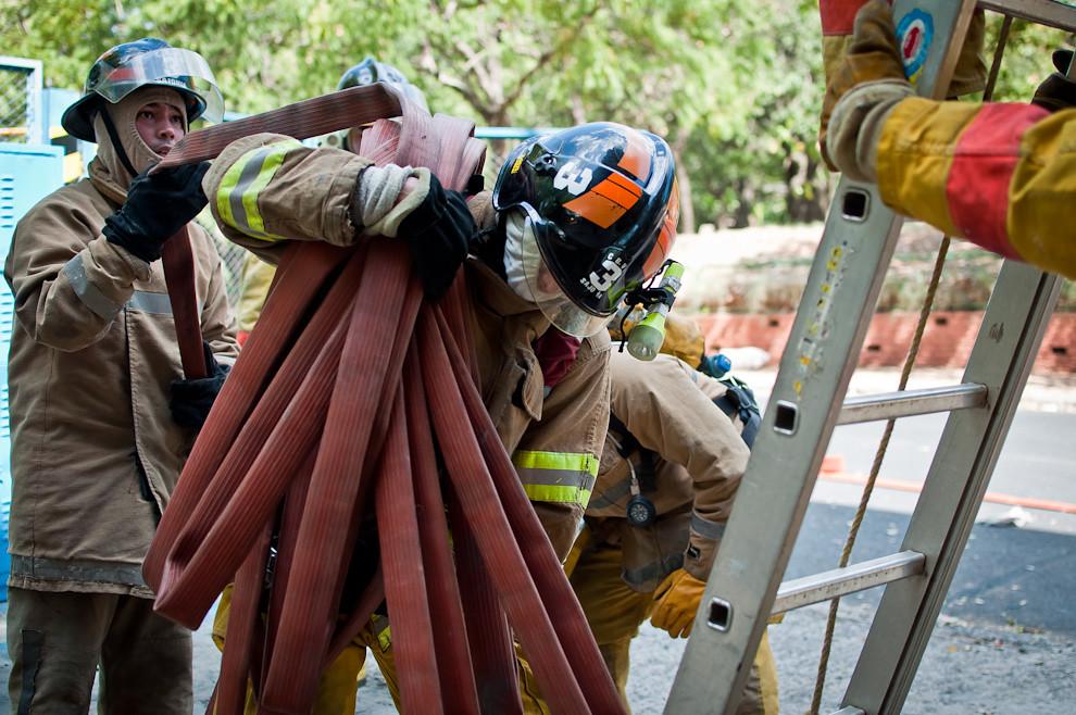 Un bombero es ordenado a subir la escala llevando en sus hombros una pesada línea de agua hasta el otro lado del edificio donde se considera que estaría el foco de un incendio. Los bomberos menos experimentados de la última camada que egresaron de la academia en el año 2011 son sometidos a duras pruebas de entrenamiento para situaciones de incendios, puede suceder que un sólo voluntario tenga que llevar una pesada línea de agua por la escalera sin otra ayuda más que su propia fuerza. Resistir y hacer el trabajo hasta el final son la consigna del éxito. (Elton Núñez).