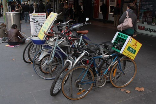 'OM Vegetarian' advertisement tied to a parked bike on Swanston Street