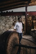 Marcelo standing infront of the an ancient mezcal mill, a traditional tool used in Mezcal production.