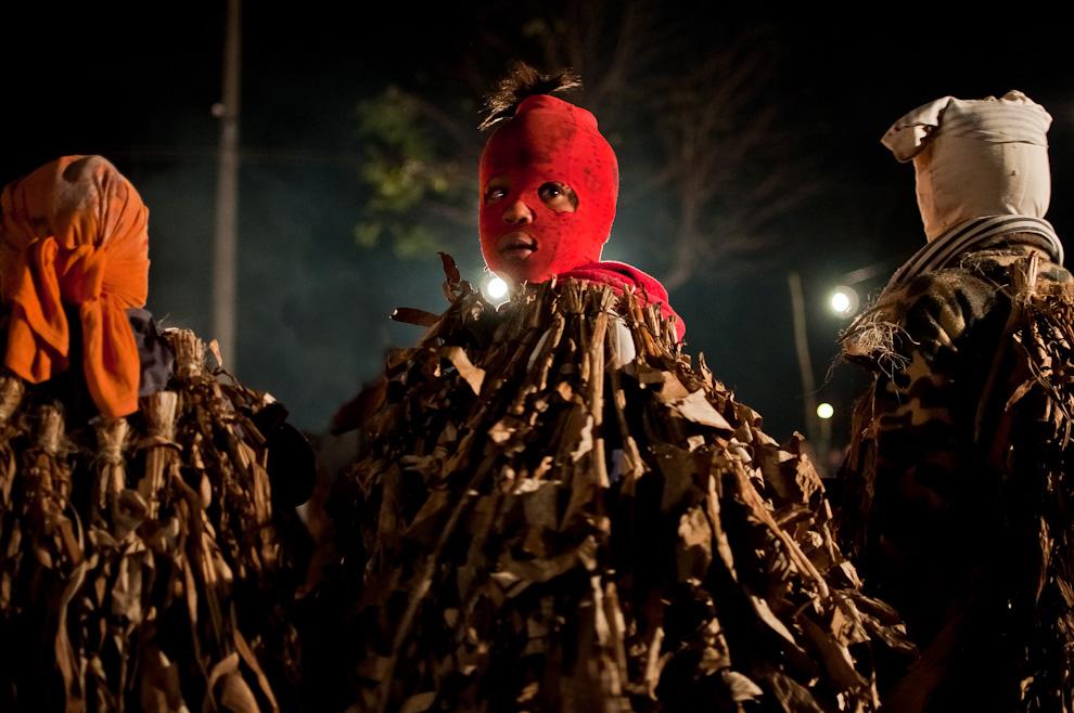 """Un muchacho disfrazado de Guaicurú espera su momento para correr y perseguir a las mujeres que participan del juego tradicional de la fiesta de San Pedro y San Pablo en el predio de una Capilla de la compañía Itaguazú de la Ciudad de Altos, Departamento de Cordillera. Lugar en donde se realiza el ritual de Kambá Ra´anga (imagen del negro) en el cual los protagonistas se visten con prendas hechas de hojas de banano, portan máscaras de madera y danzan al compás de la música de un grupo de nombre """"banda para´i"""" (de colores). Esta realización representa una ceremonia de iniciación, por ejemplo, el más conocido: el rapto perpetrado de alguna doncella por parte de un Guaicurú. (Elton Núñez)"""