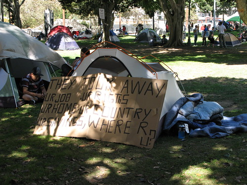 Image description: A tent with a gigantic cardboard sign leaning against it.  Sign text: THEY TOOK AWAY UR JOB UR RIGHTS UR HOME UR COUNTRY UR SAVINGS, WHERE R U?