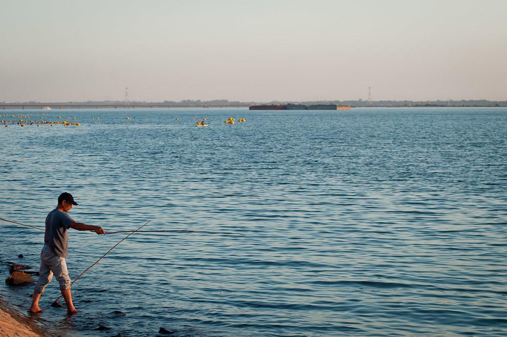 Un señor intenta pescar en la orilla del embalse del Río Paraná que corresponde a la Costanera de Encarnación en la víspera de la semana santa. (Elton Núñez)