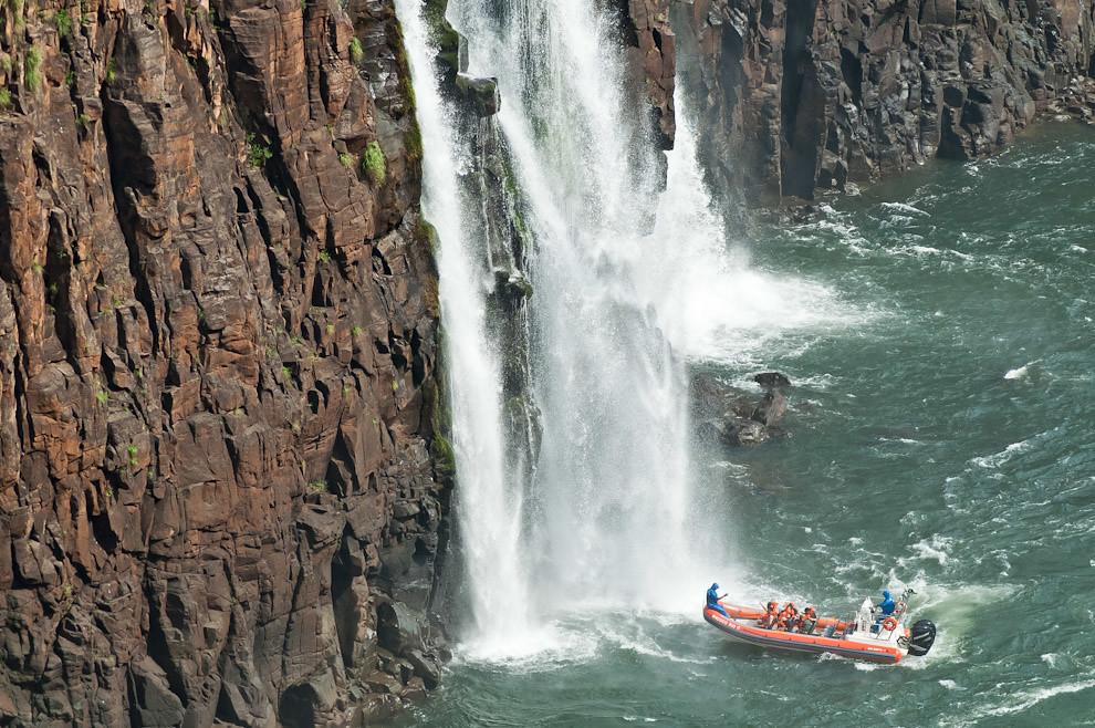 Un asistente de la organización del Parque Nacional de Iguazú, toma fotografías a los turistas que son mojados totalmente bajo las aguas de las cataratas mientras levantan los brazos lanzando gritos de vértigo y emoción, durante un tour por las aguas del Río Paraná en Foz de Iguazú. (Elton Núñez)