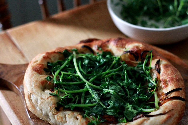 pizza topped with spring greens