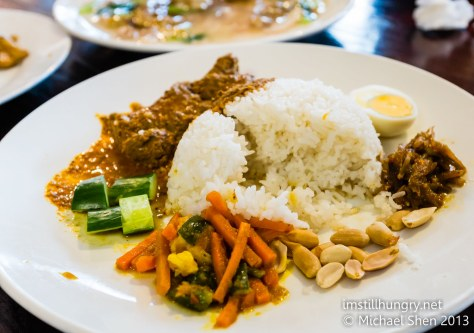 Nasi Lemak Fragrant coconut rice served with beef rendang or curry chicken, sambal anchovies, boiled egg, peanuts and pickled vegetables
