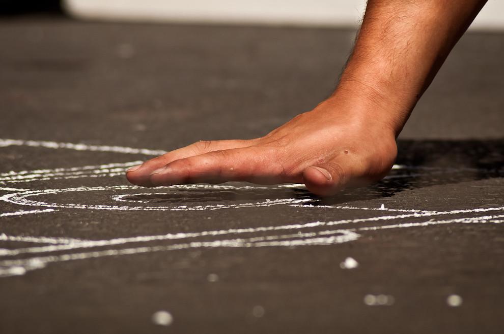 Uno de los asistentes del chef palpa la temperatura del asfalto al mediodía, el piso caliente está listo para comenzar a cocinar. (Elton Núñez)