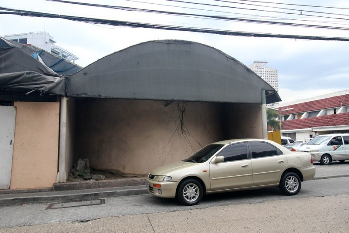 car in front of a structure with a domed roof and cracked wall
