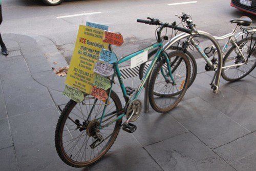 'VCE study centre' advertising tied to a parked bike on Collins Street
