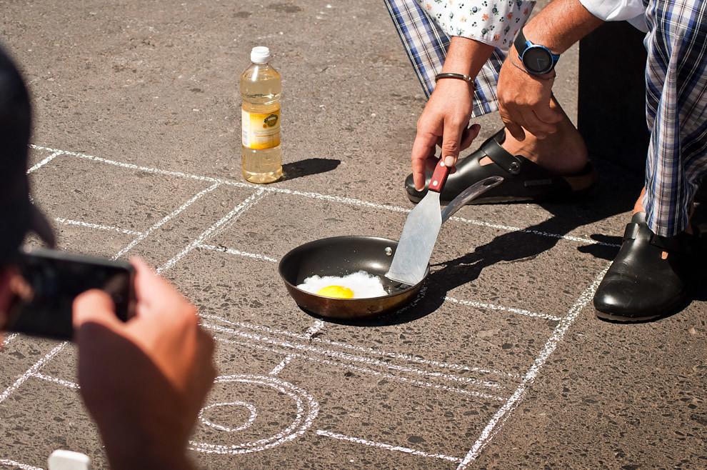 Un hombre graba un video con su celular mientras el chef cocina huevos usando solamente el calor del asfalto. No sólo huevos, sino también carnes, pancetas, polenta y tomates secos, cocinados elegantemente al estilo de Rodolfo Angenscheidt. (Elton Núñez)