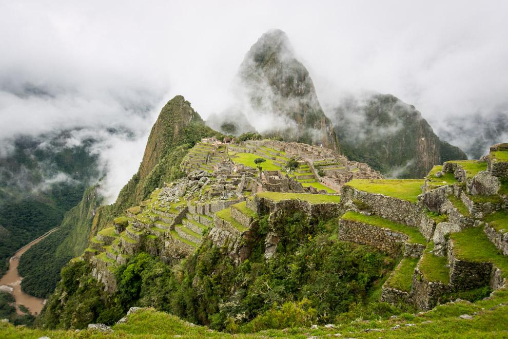 Machu Picchu, que significa en quechua Montaña Vieja, es el nombre contemporáneo que se da a un antiguo poblado andino  construido a mediados del siglo XV en el promontorio rocoso que une las montañas Machu Picchu y Huayna Picchu en la vertiente oriental de la cordillera Central, al sur del Perú y a 2490 msnm, altitud de su plaza principal. A la izquierda se ve el sector Hanan de la ciudad (con la estructura piramidal de la colina del Intihuatana) y a la derecha el sector Oriente, separadas por la plaza principal. Al fondo el Cerro Huayna Picchu. La imagen está tomada desde lo alto del sector agrícola, al sur del complejo.(Tetsu Espósito)