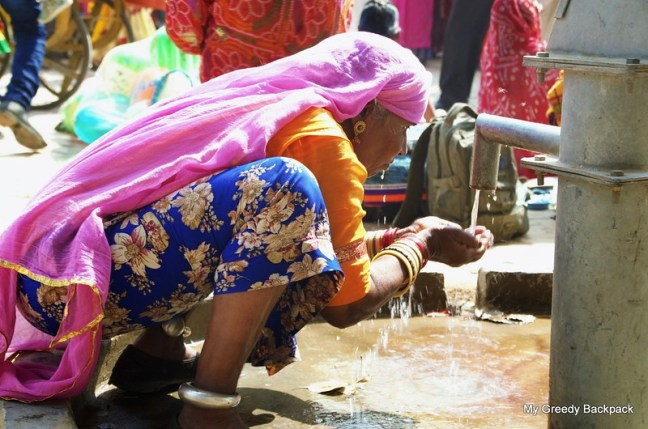 It was not that late hour of the day, but Scorching had started showing its signs. A lady kneeling down and satisfying her thirst of water in #Pushkar #Rajasthan
