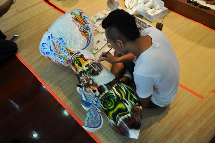 An artist paints a ghost mask at Dan Sai Folk Museum in Loei Region of Thailand. March 2015