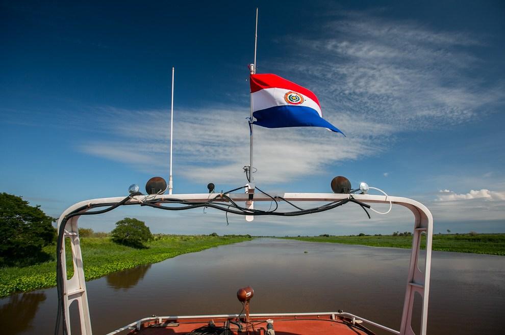 Una vista desde el techo del barco, con la bandera paraguaya en alto y un tramo angosto del Río Paraguay. (Tetsu Espósito)