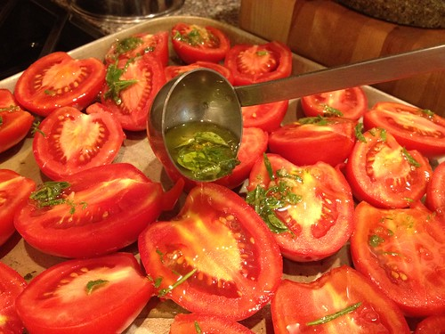 Dressing the halved tomatoes with herbs and oil