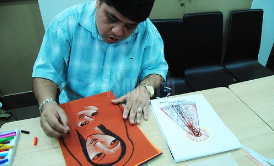 Global visual artist Aris Bagtas doing live painting using pastel colorings and colored sand paper as canvas.