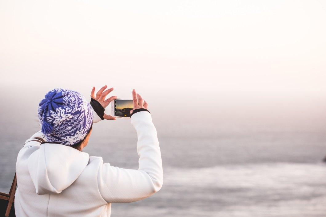 Imagen gratis de una chica tomando una fotografía del mar