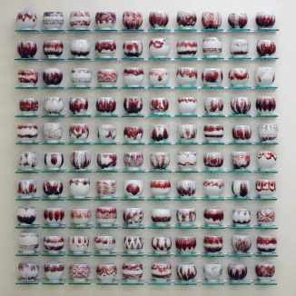 """Steven Young Lee, """"Cup Panels"""" (red), 2013, porcelain, copper inlay, glaze, glass shelving, aluminum, 46 x 50 x 4""""."""