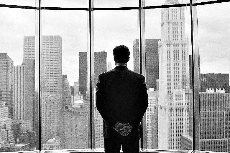 John Fisk dumnie patrzy ze swojego biura na ogromne miasto.