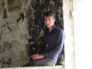 Yazidi teen smoking in stairwell