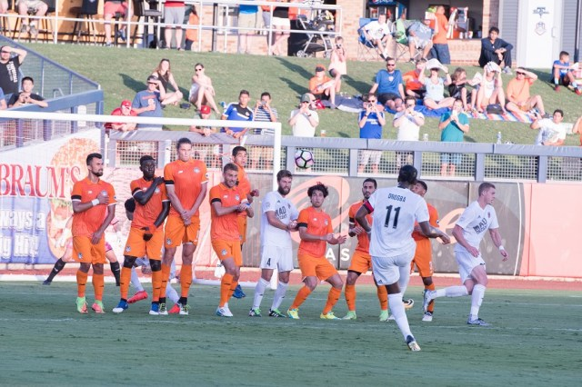 Phoenix Rising FC's Didier Drogba, bottom, attempt to hit a free kick over the wall in the first half against Tulsa Roughnecks FC Saturday, July 22 at ONEOK Field in Tulsa, Okla. Photo by Lori Scholl