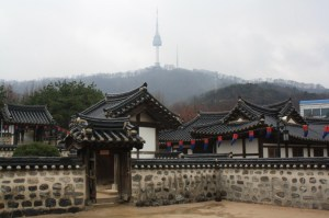 Traditional Korean folk houses. Behind is the N Seoul Tower.